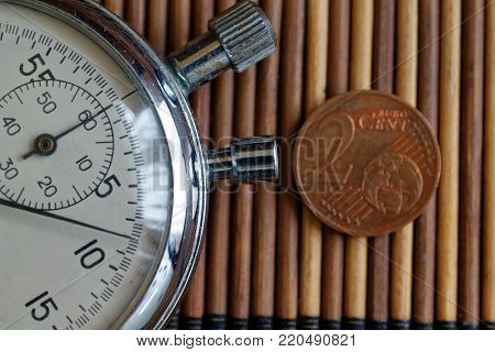 Stopwatch and coin with a denomination of two euro cents on wooden table background