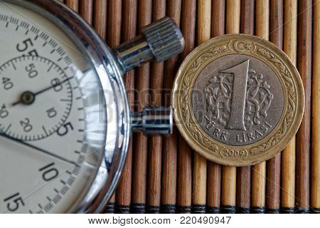Stopwatch and coin with a denomination of twenty euro cents on wooden table background