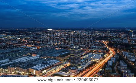 Munich, Germany - December 14, 2016: Evening Munich birds eye panoramic cityscape view with bright night lights of BMW plant and headquarters