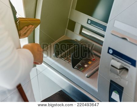 Side view of woman using ATM holding wallet an pressing the PIN security number on the keyboard automatic teller machine