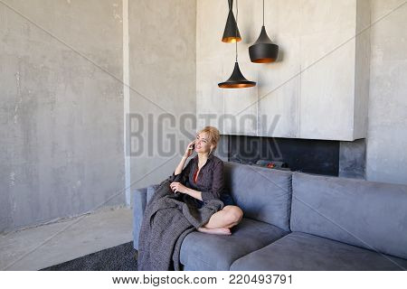 Pretty attractive woman takes phone by hand and spends it on touch screen to answer husband's incoming call, chatting and laughing happily, sitting on gray soft sofa in lotus pose wrapped in plaid in stylish living room with gray walls.