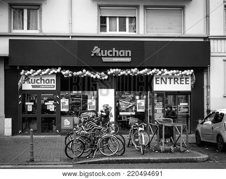 STRASBOURG, FRANCE - DEC 4, 2017: Black and white Auchan Supermarket entrance in French neighborhood on a winter snow day with customers exiting the entrance of the store