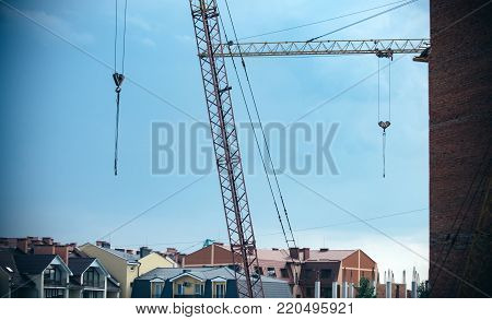 Building crane in residential district on blue sky background. Construction equipment, machine. Real estate, dwelling, property concept. Architecture, structure, design.