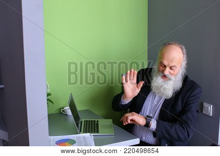 Oldie modern man study new and modern technologies, learn to work with bluetooth headsets and iWatch, sitting and working on laptop in cozy computer cafe on sunny day. Elderly man with long gray beard of European appearance dressed in black classic suit