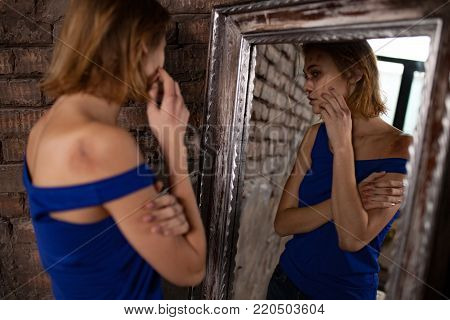 Beaten young woman victim of domestic violence and abuse stands near mirror and views bruises and wounds on her bloody face. Сoncept of domestic violence, sexual violence and cruelty.