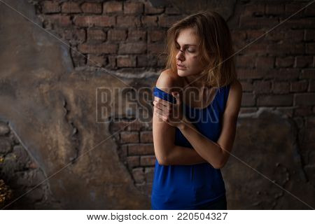 Beaten sad woman victim of domestic violence and abuse stands with bruises and wounds on her face and body against background of brick wall.  Сoncept of domestic violence, sexual violence and cruelty.