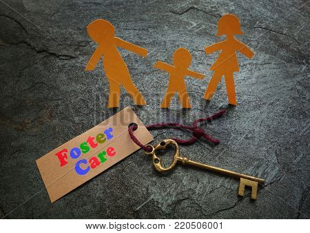 Paper foster care family of three with gold key
