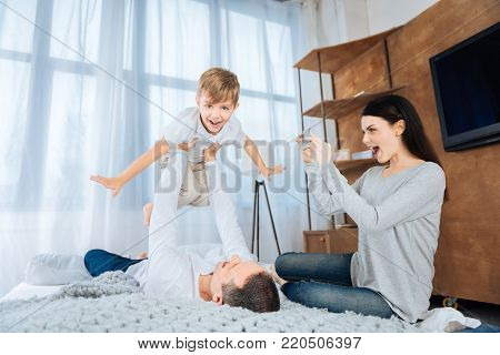 Funny games. Upbeat young woman sitting on the bed and filming her husband lifting up his son, playing with him