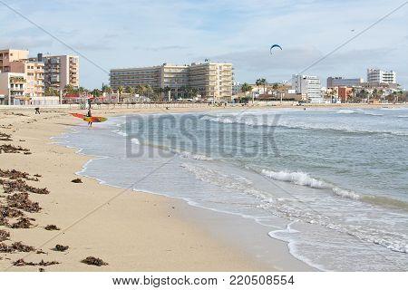 PLAYA DE PALMA, MALLORCA, SPAIN - DECEMBER 14, 2017: Kitesurfing on the winter beach on a windy day on December 14, 2017 in Mallorca, Balearic islands, Spain