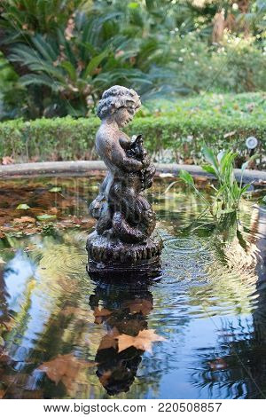 MALAGA, SPAIN - DECEMBER 19, 2017: Detail of sculpture in pond among green vegetation in Jardin de la Concepcion on December 19, 2017 in Malaga, Spain
