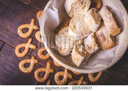 Sliced bread lies on the crackers in a bowl. The sliced baguette lies beautifully in a bowl on parchment paper. The cookie lies on the wooden surface around the plate with bread.