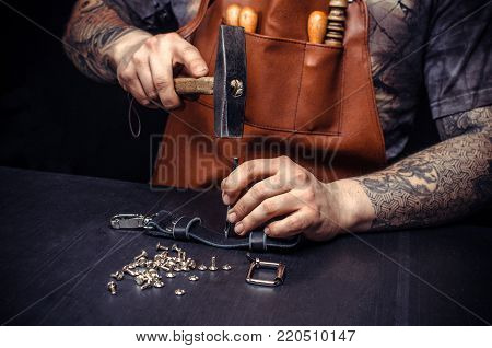 Handyman creating leatherwork at his workplace. Leather Craftsman producing leather workpiece in his leather shop.