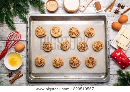 Cooking cinnamon rolls. Christmas baking background. Preparation raw dough traditional sweet dessert buns danish pastry. Baking ingredients flat lay. Top view