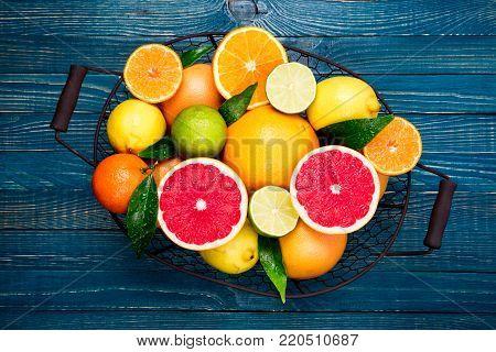 Citrus fruits background. Assorted fresh citrus fruits with leaves. Fruits in basket orange, grapefruit, lemon, lime, tangerine. Top view