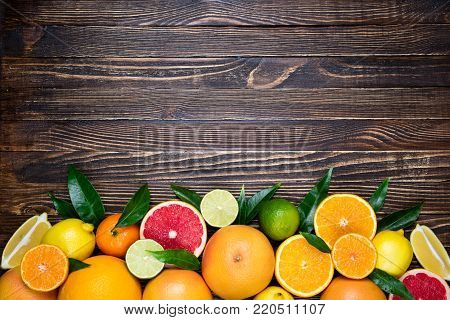 Citrus fruits background. Fruits in basket orange, grapefruit, lemon, lime, tangerine on wooden table. Assorted fresh citrus fruits with leaves. Top view, flat lay. Copy space