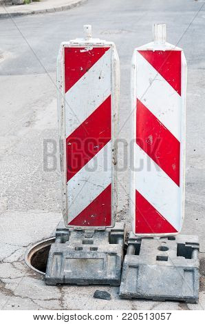 Road sign. Street reconstruction or construction barricade caution signs cover the open hole of manhole on the road as a precaution vertical image