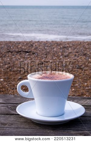 a white coffee cup and saucer full of cappuccino coffee with chocolate on top, on a wooden table on a pebble beach in the winter with the sea, sky and cliffs in the background,