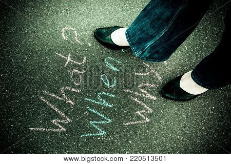 Woman in shoes standing on the asphalt road. On the road with chalk painted