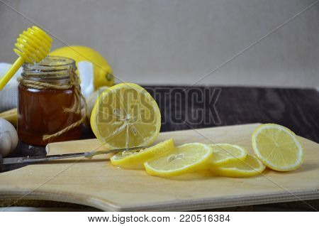 Sliced lemon slices on a table for making lemonade, tea, drink, honey, garlic, turmeric, ginger for making a hot drink for cold treatment on wooden table