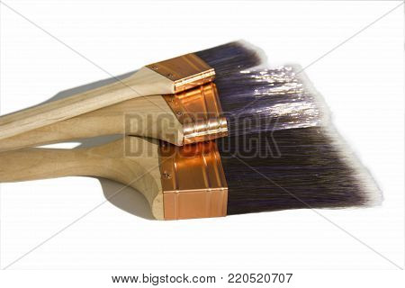 Three large synthetic high quality paint brushes on a white isolated background.