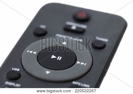 Close-up of a dark grey remote control, focused on the Play/Pause button, isolated on white background.