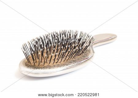Close-up of an used hairbrush, isolated on white background
