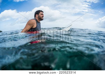 Surfer waits the wave on line up with surf board