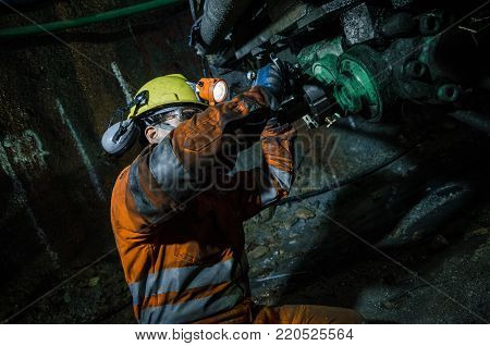 Miner fixing the mineral extraction machine in the mine