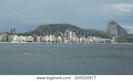 Lonely woman adrift on a paddleboat overlooking iconic Copacabana Beach in Rio de Janeiro, Brazil with the Sugarloaf Mountain the far right of the image