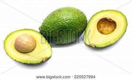 Sliced and whole avocado (Persea americana, alligator pear) with a stone isolated on white background