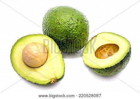 Whole avocado (Persea americana, alligator pear) and its halves with a stone isolated on white background