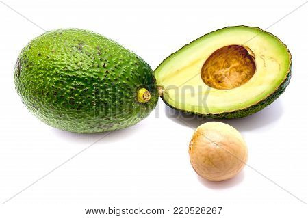 Avocado (Persea americana, alligator pear) slices and one whole avocado with a stone isolated on white background