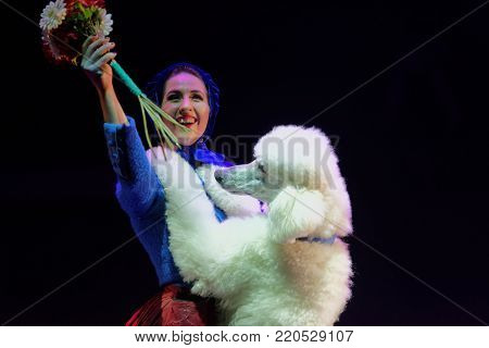 ST. PETERSBURG, RUSSIA - DECEMBER 28, 2017: Victoria Akimova as Gerda with trained dogs in the circus show Snow Queen by Great Moscow circus. The show created by Zapashny brothers circus