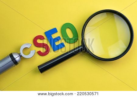 Magnifying glass, alphabet abbreviation SEO and robot arm on vivid yellow background using as SEO Search engine optimization concept.
