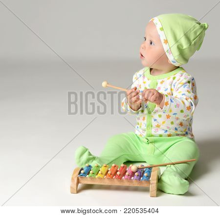 Portrait of Infant child baby boy kid toddler sitting in light green body and play with xylophone toy on gray background