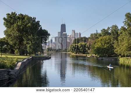 A man rowing a scull along the South Lagoon in Lincoln Park with downtown Chicago in the distance. USA