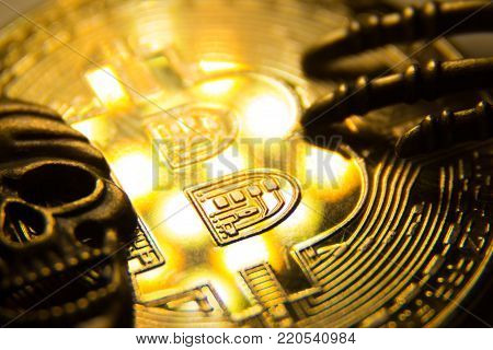 The concept of piracy with crypto currency. ymbol of a pirate skull and fingers of a skeleton on a gold bitcoin with light spots. Macro. Close up.