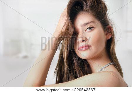 Beautiful green eyed young woman combing her hair