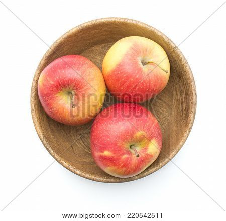 Three apples (Evelina variety) in a wooden bowl top view isolated on white background red yellow