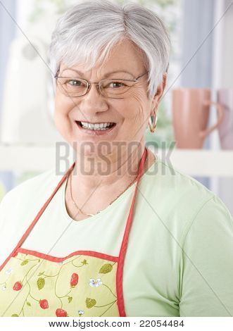 Portrait of senior woman smiling happily, wearing cooking apron.?