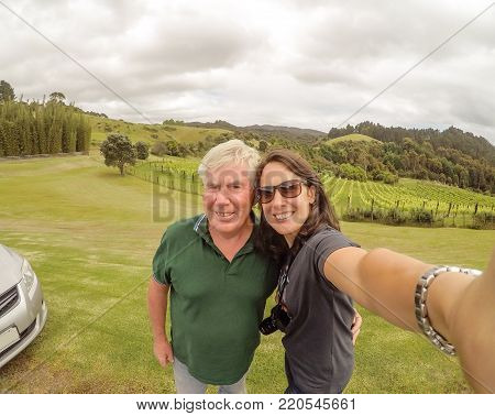 Retired father and middle aged daughter taking selfie - happy smiling family of tourists travelling together at a vineyard in Northland, New Zealand, NZ. Models are of European Swiss descent.