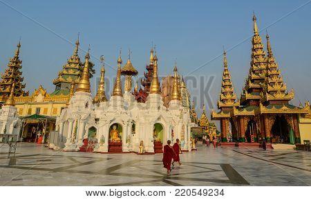 Yangon, Myanmar - Feb 26, 2016. Buddhist monks walking at Shwedagon Pagoda in Yangon, Myanmar. The Pagoda is believed by Buddhists to be around 2500 years old.