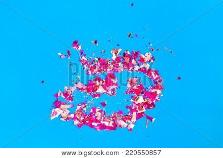 Shards of sequins slim a broken stained glass on a bright blue background, abstract festive background