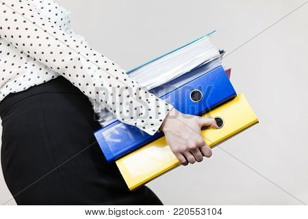 Woman holding many heavy colorful binders with documents. Office, bookkeeping objects concept.