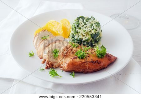 Chicken breast with orange fillets and spinach rice on a white plate, healthy diet dish with low calories, selective focus, narrow depth of field