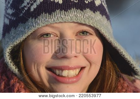 Portrait of a beautiful smiling Caucasian teenage girl on a snowy winter background
