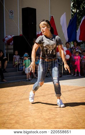 Komsomolsk-on-Amur, Russia, 1 August, 2015. girl dances breakdance in the square with spectators