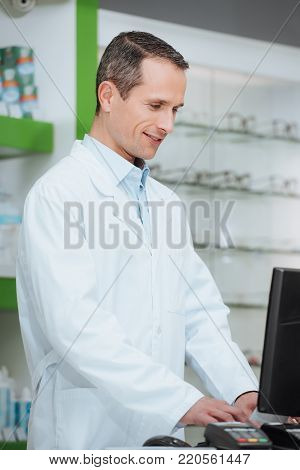 side view of optometrist working on computer in optics