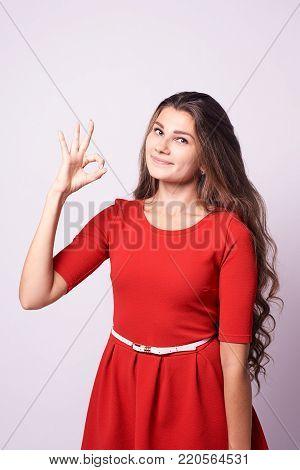 Beautiful girl. Gesture consent. Portrait brunette. White background.