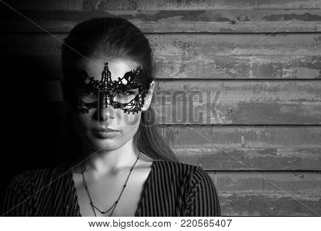 Black and white portrait of young beautiful lady in elegant masquerade mask. Face in the shadows. Black lace mask on the eyes. Professional makeup